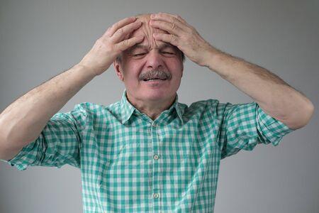 Thinking caucasian senior man holding hands on head.