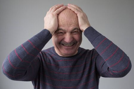Senior hispanic man laughing out loud with closed eyes and hand on his head Stockfoto - 134604565