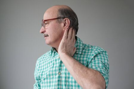 Frustrated senior holding hand on his neck while standing against grey background Stockfoto - 134604571