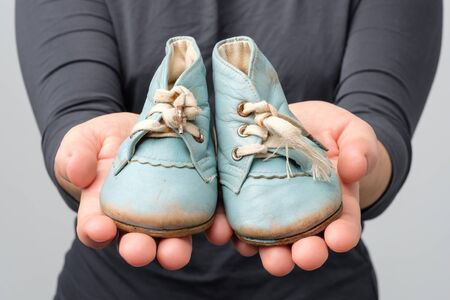 Woman holding old retro baby shoes. Close up view