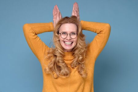Mature woman with curly hair standing with funny face and bunny ears gesture
