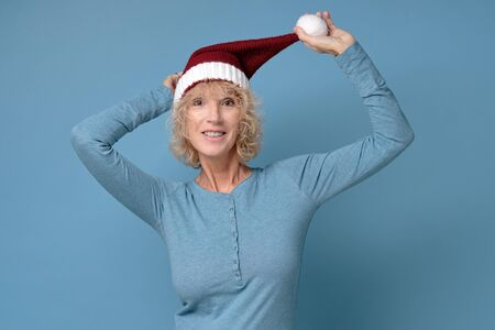 Pretty christmas woman in red santa hat, smiling isolated on blue background Stockfoto - 136716459