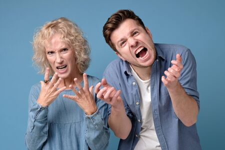 Young man and mature woman with a mad aggressive expression screaming Stockfoto - 136716460