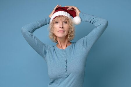 Pretty christmas woman in red santa hat, smiling isolated on blue background