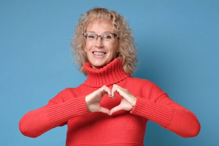 Mature blonde woman girl inred sweater posing showing shape heart with hands.