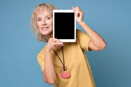 Senior woman show display of tablet with black screen and smiling