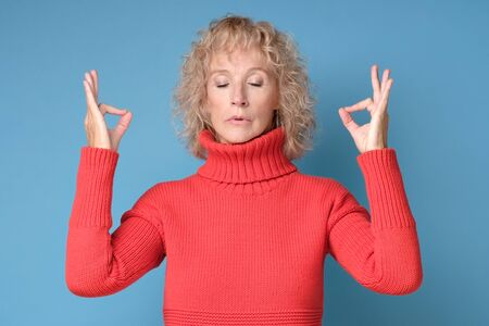 Restful blonde female in red sweater feels relaxed, tries to concentrate