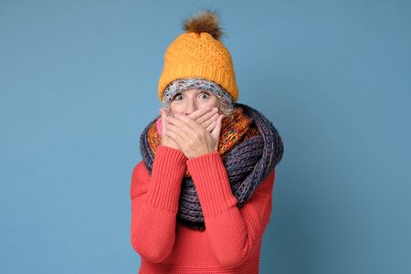 Woman in winter clothes having astonished expression, covering mouth with hands