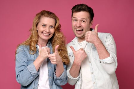 Sister and brother approving doing positive gesture with hand, thumbs up Stockfoto