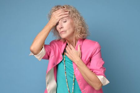 Mature caucasian woman in colored clothes touching her thead feeling stress Stockfoto