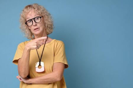 Happy mature woman in glasses and yellow shirt showing finger away