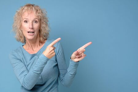 Mature blonde cheerful woman looking aside pointing.