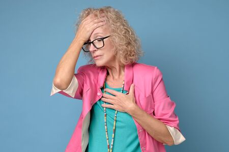 Stressed upset middle aged old woman suffering from terrible headache Stockfoto - 136960508