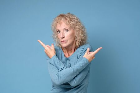 Mature blonde woman pointing to both sides with fingers in different direction Stock Photo