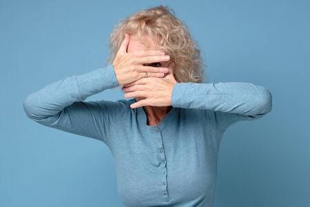 Mature woman covering her face with his hands and spies, hiding her eyes Stockfoto - 136960512
