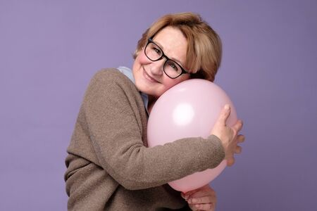 Caucasian senior woman in glasses and sweater hugging pink balloon