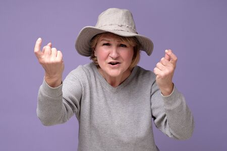 Mature woman in summer hat standing and looking at camera and screaming.