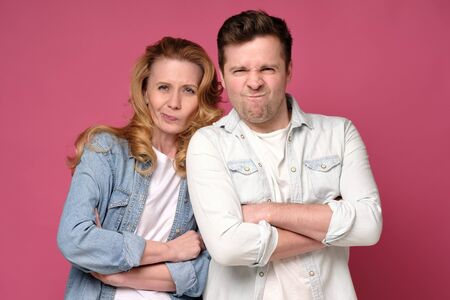 Mature couple frowning with their arms crossed listening to bad news.