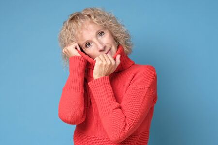 Blonde woman in red sweater looking calm smiling being self confident.