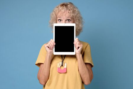 Mature woman hiding his face behind portable computer device on blue background Stockfoto