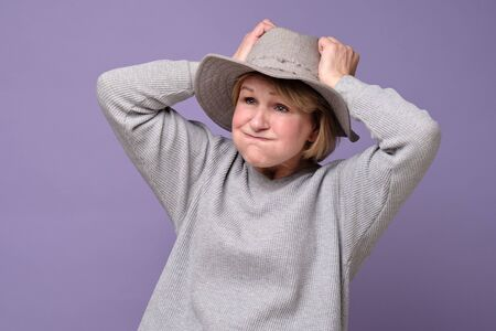 Mature woman in summer hat holding head in hands feels unhealthy. Stockfoto - 136916571