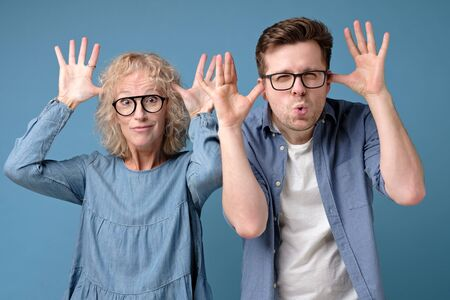 Mature caucasian couplemother and son teasing each other on blue background