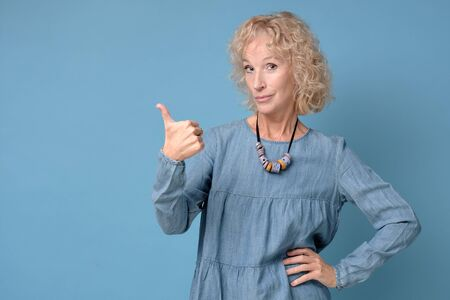 Happy senior blonde woman with thumbs up approving your choice. isolated on blue background
