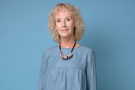 Modern elderly blonde woman standing smiling against blue background. Positive facial human emotion.
