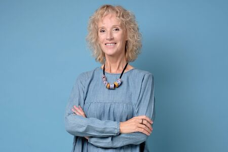 Modern elderly blonde woman standing smiling at the camera with folded arms against blue background
