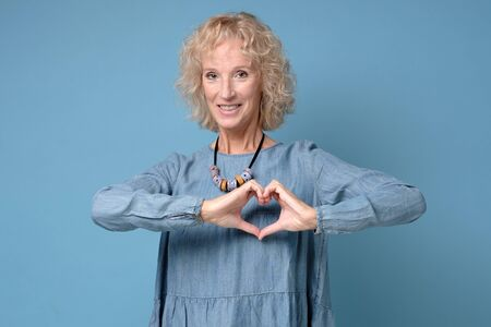 Love, heart shape, peace. Cute attractive smiling blonde woman shows heart sign with help of her hands on blue background