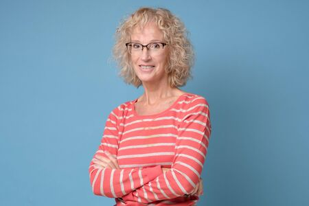 Attractive caucasian smiling mature woman with blond hair in glasses smiling at camera standing with folded hands. Studio shot Stockfoto