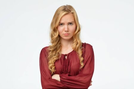 Beautiful girl with blonde long hair frowning her face in displeasure, keeping arms folded. Attractive young woman in closed posture. Studio shot