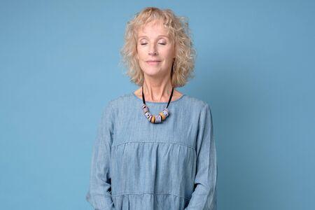Positive senior lächelnde Frau mit geschlossenen Augen stehend meditierend vor blauem Hintergrund Standard-Bild