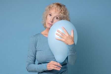 Senior woman r holding a blue balloon being alone on her Birthday party Stockfoto - 137763032