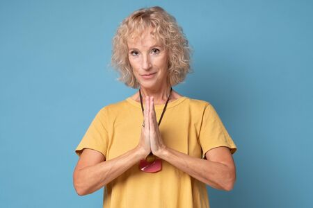 Portrait of happy mature woman with blonde hair in yellow t-shirt, holding hands in pray over chest Stockfoto - 137763029