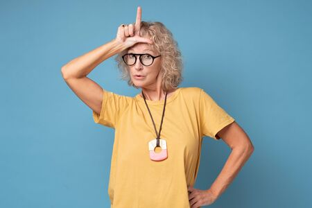 Annoyed woman, showing loser sign standing with disrespectful expression