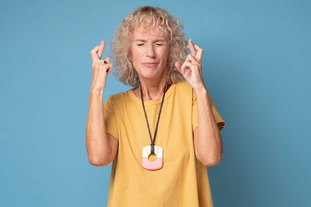 Senior caucasian woman in yellow clothes crossing fingers wishing luck Stockfoto - 137390750