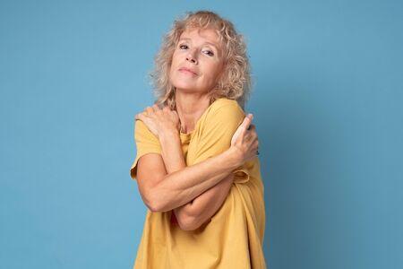 Mature blonde femal hugging herself, having joyful cheerful facial expression