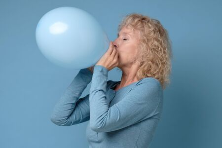 Senior blonde woman preparing for party blowing up blue balloon