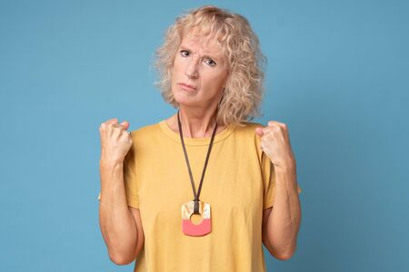 Angry old woman making fists on blue background Stockfoto