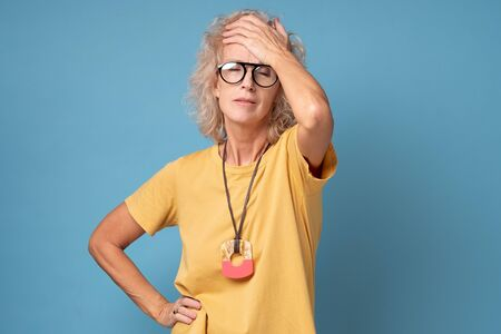 Middle aged woman suffering from headache holding her hand on forehead.