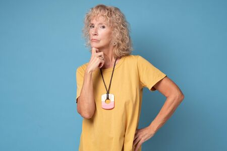 Senior blond woman listening interlocutor, thinking, waiting the results