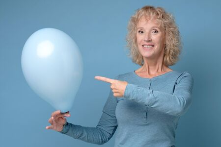 Senior woman r holding a blue balloon being alone on her Birthday party