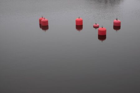 Several red buoys in the sea calm water Reklamní fotografie