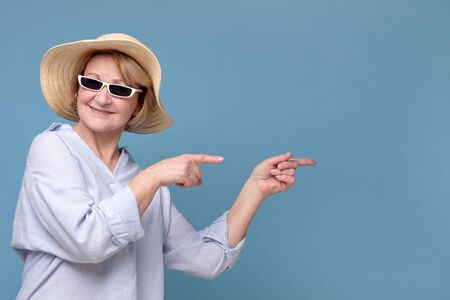 Woman insummer hat and sunglasses pointing aside having great mood smiling