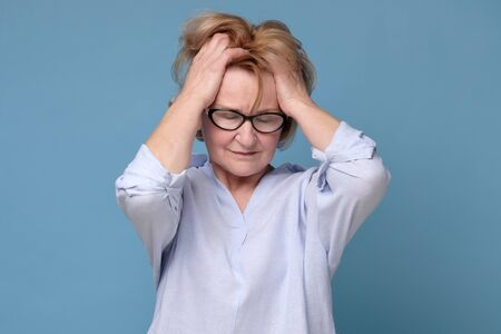 woman in glasses holding hand to her forehead having migraine or head ache. Stockfoto