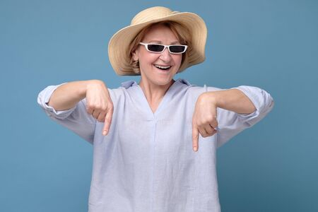 Senior woman insummer hat and sunglasses pointing down having great mood Stockfoto - 137700130
