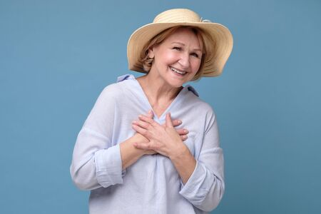 Happy joyful senior lady in summer hat looking at camera and smiling Stockfoto