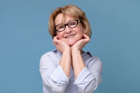 Beautiful senior woman in glasses looking with smile at camera.