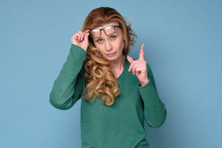 Mature business woman wearing glasses pointing with finger up